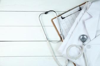 Estetoscópio, prancheta e uniforme de médico na mesa de madeira branca e limpa