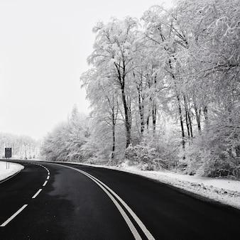 Estrada vazia com paisagem coberta de neve. Belo fundo sazonal de inverno para transporte e automóveis.