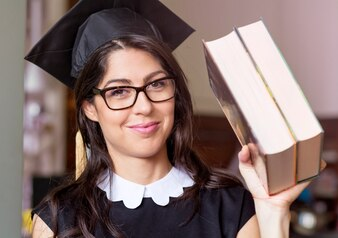 Estudante com tampão da graduação que prende dois livros