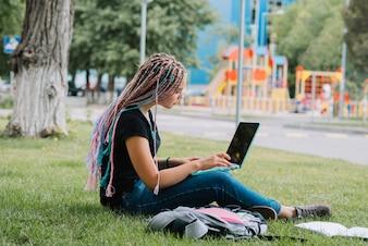 Estudante elegante no parque com laptop