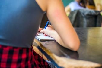 Estudante estudando escrever notas em um caderno em uma mesa