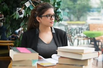 Estudante pensativa sentada à mesa com livros