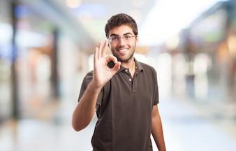 Estudante que mostra o sinal aprovado