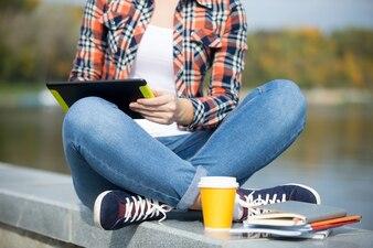 Estudante sentado turco na ponte com tablet