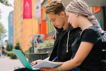 Estudantes que trabalham com laptop