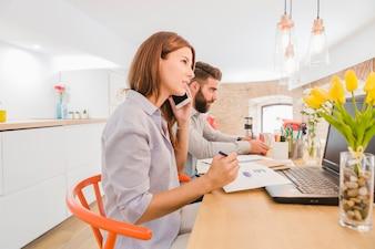 Executiva falando telefone no escritório