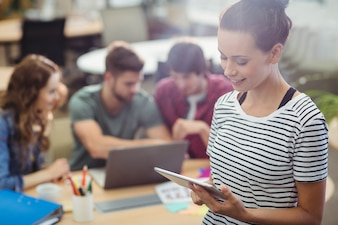 Executivo de negócios fêmea que usa a tabuleta digital