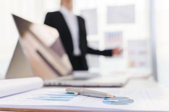Executivos que usam laptop e Cartas financeiras na reunião o