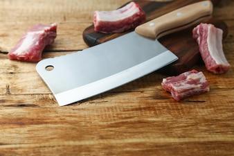 Faca cortante e costelas na tábua de madeira