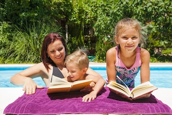 Família relaxante em piscina com livros