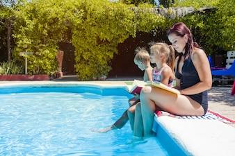 Família sentado ao lado da piscina segurando livros