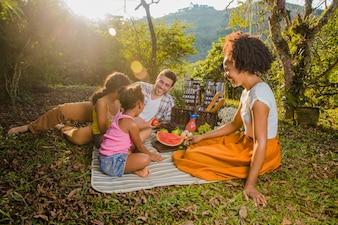 Família tendo um piquenique ao pôr do sol