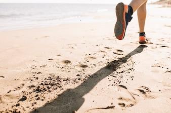 Feche a vista do homem jogging na areia