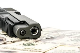 Feche acima da imagem da pistola e do dólar.