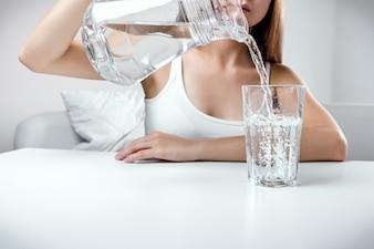 Feche acima da jovem que derrama água pura fresca do jarro em um copo