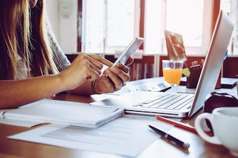 Feche acima de uma mão de mulher usando um telefone inteligente com laptop em uma mesa no escritório