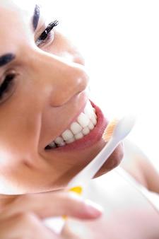 Feche acima do retrato da mulher nova bonita que escolhe seus dentes