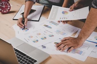 Feche acima dos executivos que trabalham com o original do negócio durante a discussão na reunião.