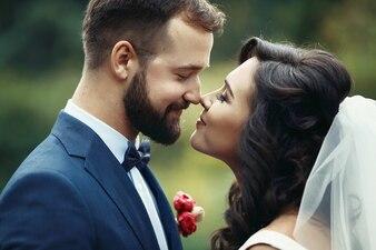 Feliz casal de recém-casados olhando um para o outro em um parque
