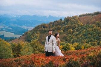 Feliz casal recém-casado posando nas montanhas