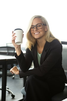 Feliz empresária sentada com café no escritório