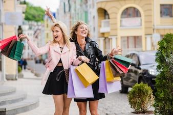 Feliz garotas loiras de pé segurando bolsas