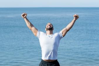 Feliz homem forte comemorando sucesso esportivo no mar
