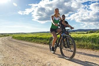 Feliz jovem casal em bicicleta no campo