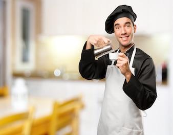 Feliz jovem cozinheiro usando uma chaleira