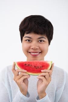 Feliz mulher asiática segurando uma fatia de melancia