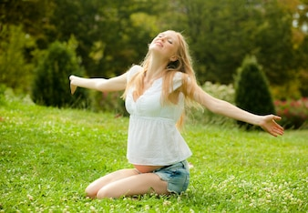 Feliz mulher grávida na grama macia