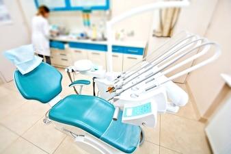 Ferramentas profissionais de dentista e cadeira no consultório odontológico.