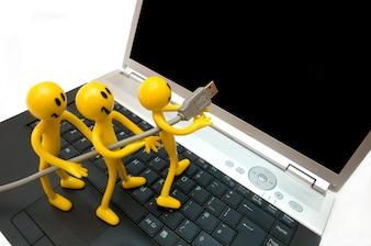 Figuras de ação que ligam um laptop