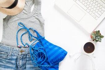 Flat lay of summertime clothing with blue stripe bikini, laptop e xícara de café no fundo branco