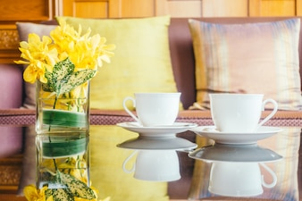 Flor de vaso e copo de café branco sobre mesa e travesseiro no sofá