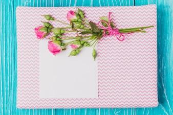 Flores e pedaço de papel sobre o livro