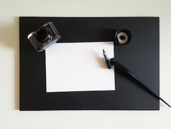Folha de papel, caneta e tinta de preto na mesa de escritório preto.