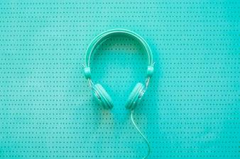 Fones de ouvido em fundo azul-turquesa