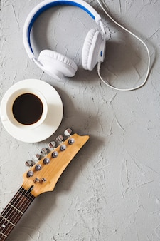 Fones de ouvido, guitarra e café