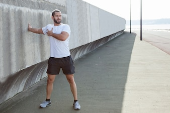 Forte Sporty Man Stretching Arm Outdoors