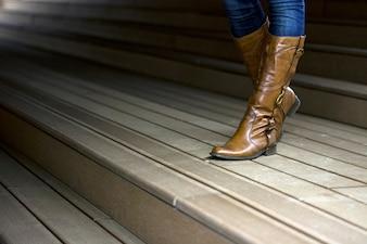 Foto de mulher de couro com botas na trilha de madeira