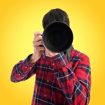 Fotógrafo tomando uma foto em fundo colorido