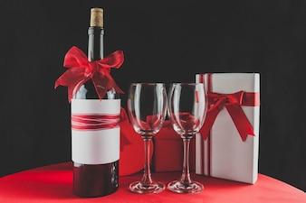 Frasco de vinho com uma fita vermelha e dois copos vazios