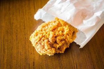 Fried Chicken Wings no saco de papel na tabela de madeira.