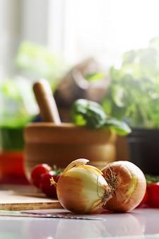 Fundo da cozinha comendo o conceito de comida. Cebola na mesa. Legumes na tabela. Processo de cozimento.