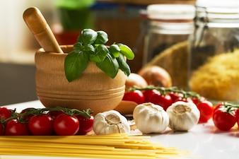 Fundo da cozinha comendo o conceito de comida. Closeup of Cooking Process. Legumes na tabela. Cozinhando de macarrão italiano.