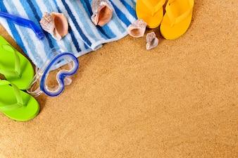 Fundo da praia com máscara de mergulho e chinelos