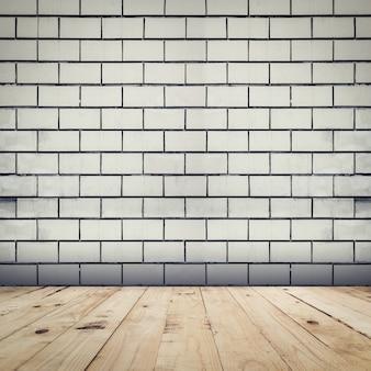 Fundo de parede de tijolos brancos e piso em madeira.