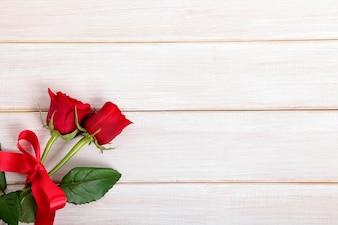 Fundo do Valentim de rosas vermelhas na placa de madeira branca