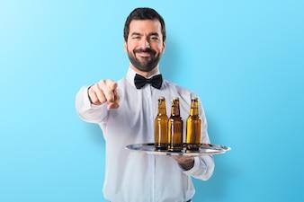 Garçom com garrafas de cerveja na bandeja apontando para a frente em fundo colorido